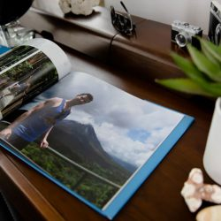 A custom photo book on a wood table with a picture of a man standing in front of a mountain | Motif