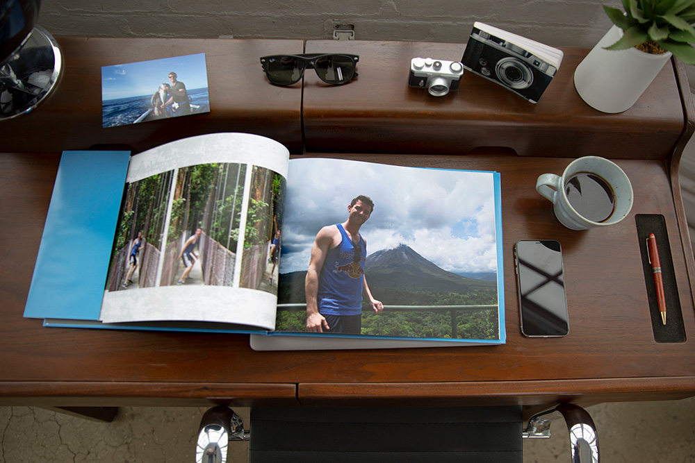A photo book on top of a dark brown desk | Motif