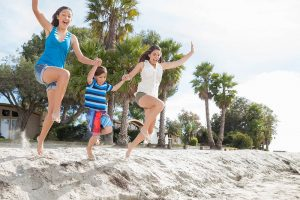 A family jumping in the sand at a beach | Motif