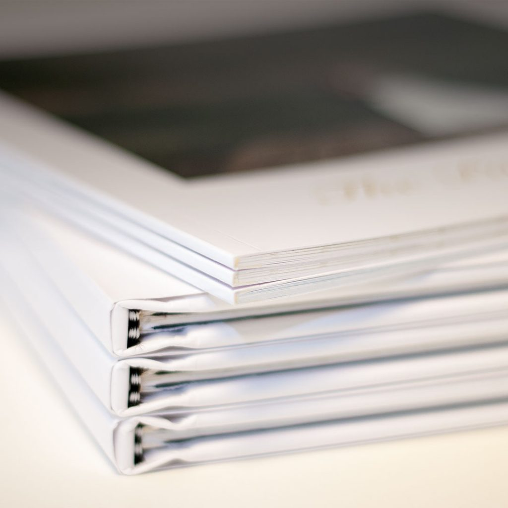 Four completed photo books stacked on top of each other | Motif