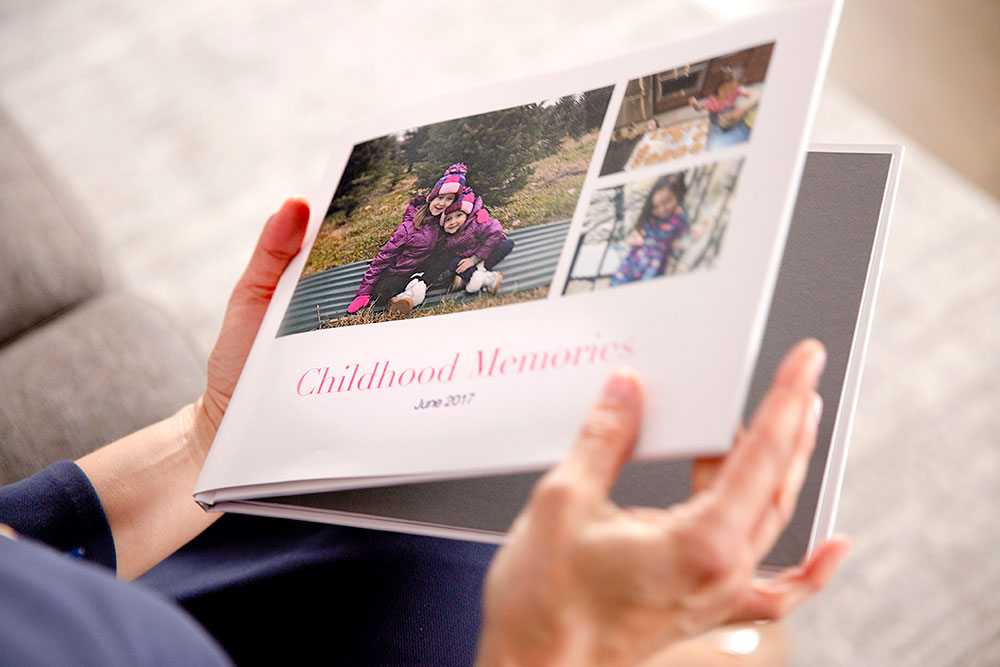 A person holding a custom photo book | Motif