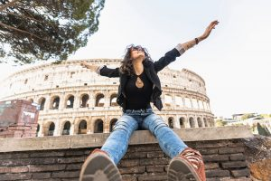A girl sitting in front of the Colosseum in Rome   Motif