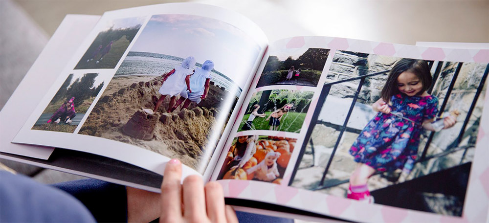 Someone looking through a customer photo book of their children | Motif