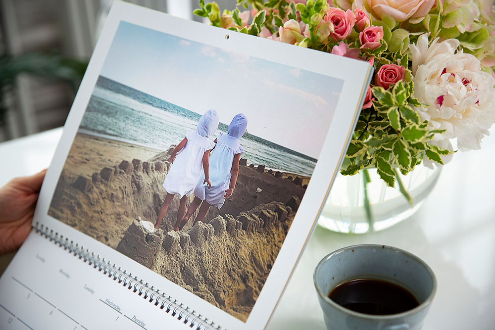 A custom calendar with a picture of two girls walking through a sand castle | Motif