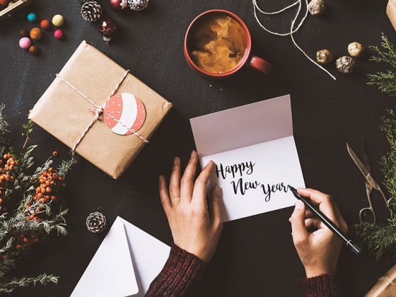 """Someone writing """"Happy New Year"""" on a custom Motif card surrounded by decorations 