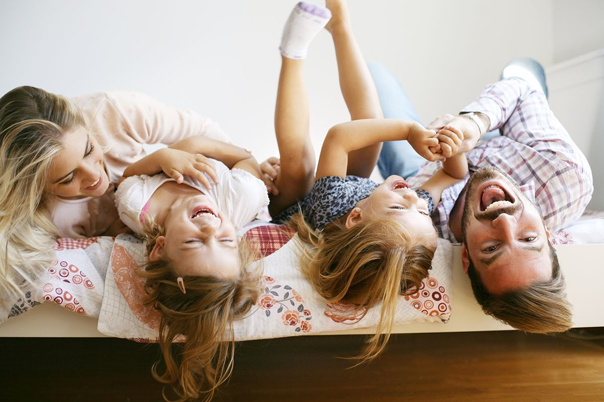 A family taking a group photo hanging upside down on a bed | Motif