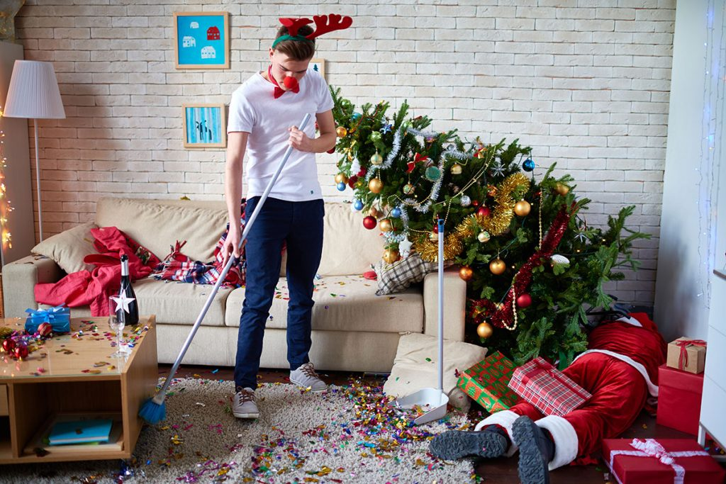 A guy cleaning up after a Christmas party   Motif