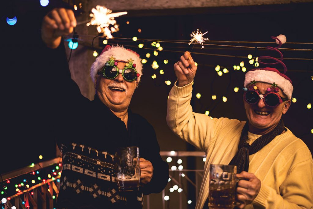 Senior citizen friends holder sparklers celebrating Christmas | Motif