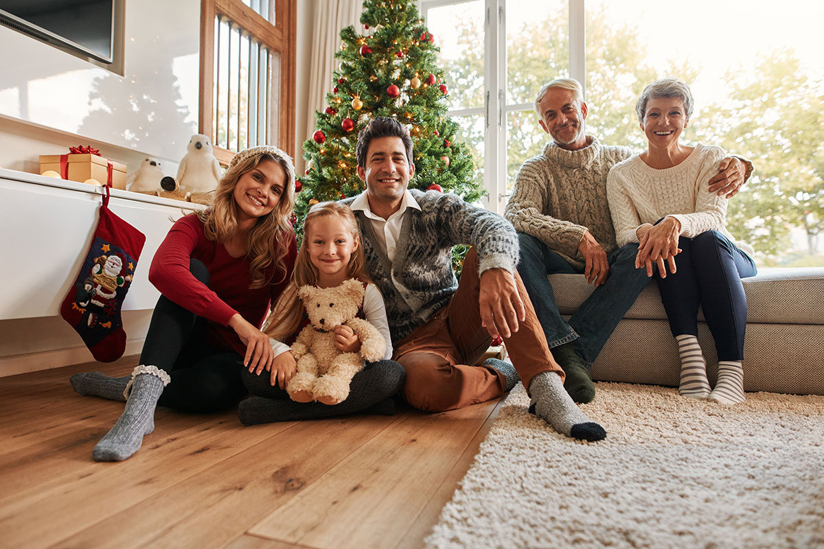 A family portrait of three generations in front of a Christmas tree   Motif