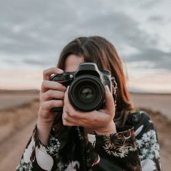 A woman taking a picture with a DSLR camera | Motif