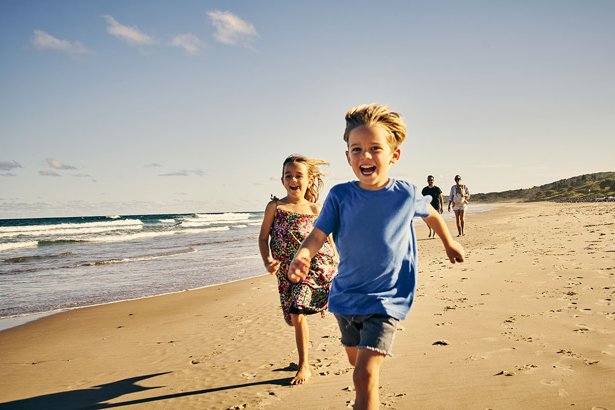 Two younger kids running on the beach with their parents walking behind   Motif