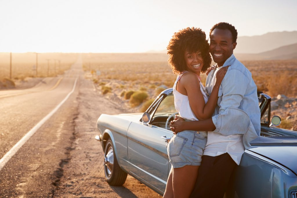A couple hugging against a car during the golden hour | Motif