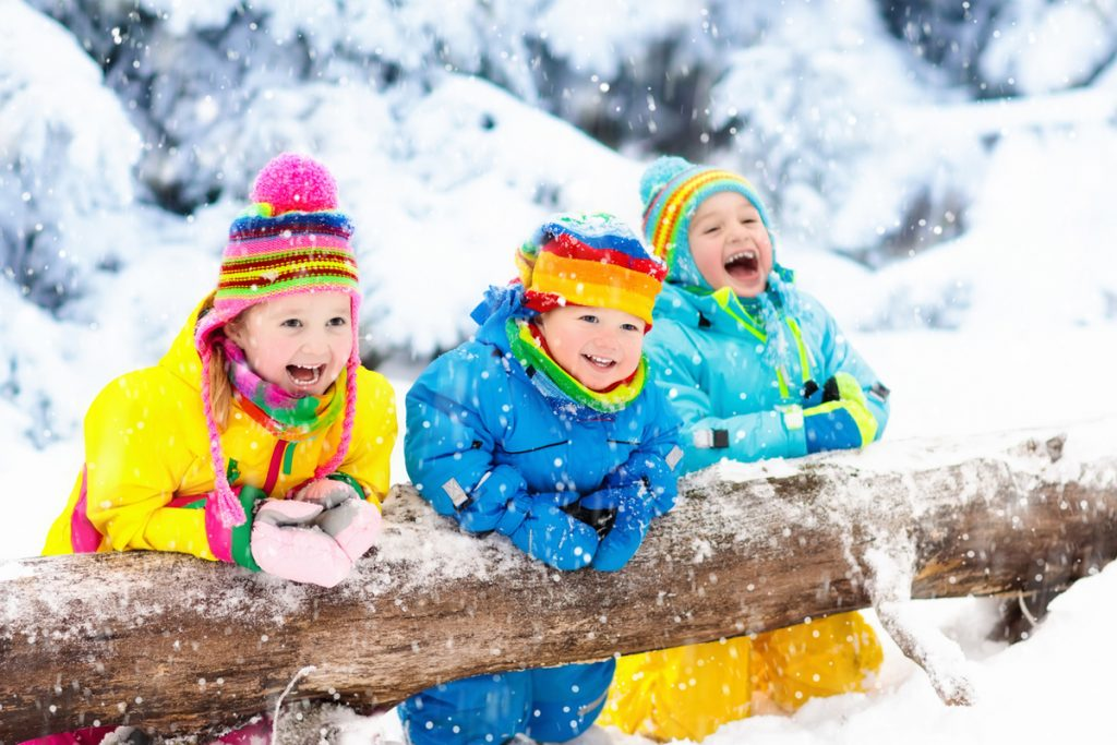 Kids in Colorful Coats Contrasted Against Snowy Backdrop