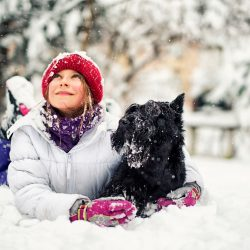 A girl and her dog laying down in the snow | Motif