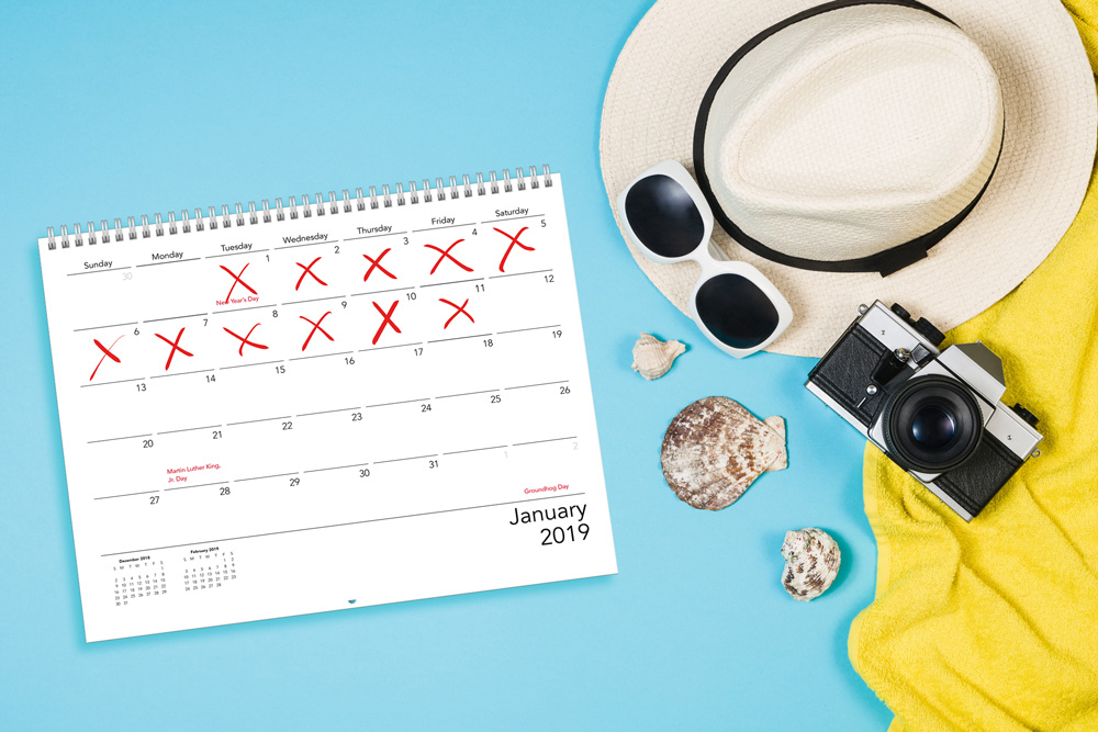A custom calendar next to a sun hat, sunglasses, seashells, a camera and towel | Motif