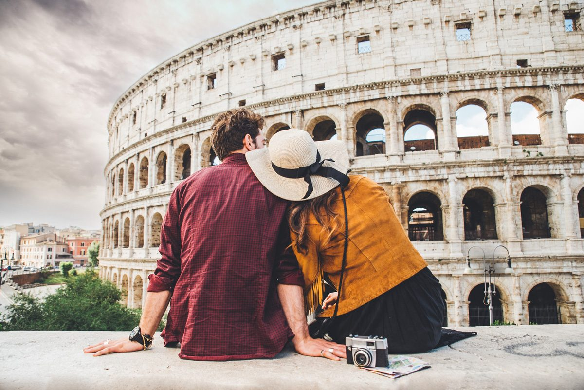 A couple sitting together outside the Roman Colosseum | Motif