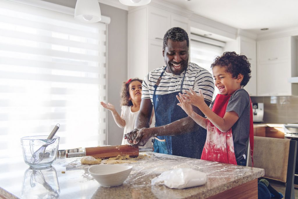 A father and his two kids baking in the kitchen | Motif