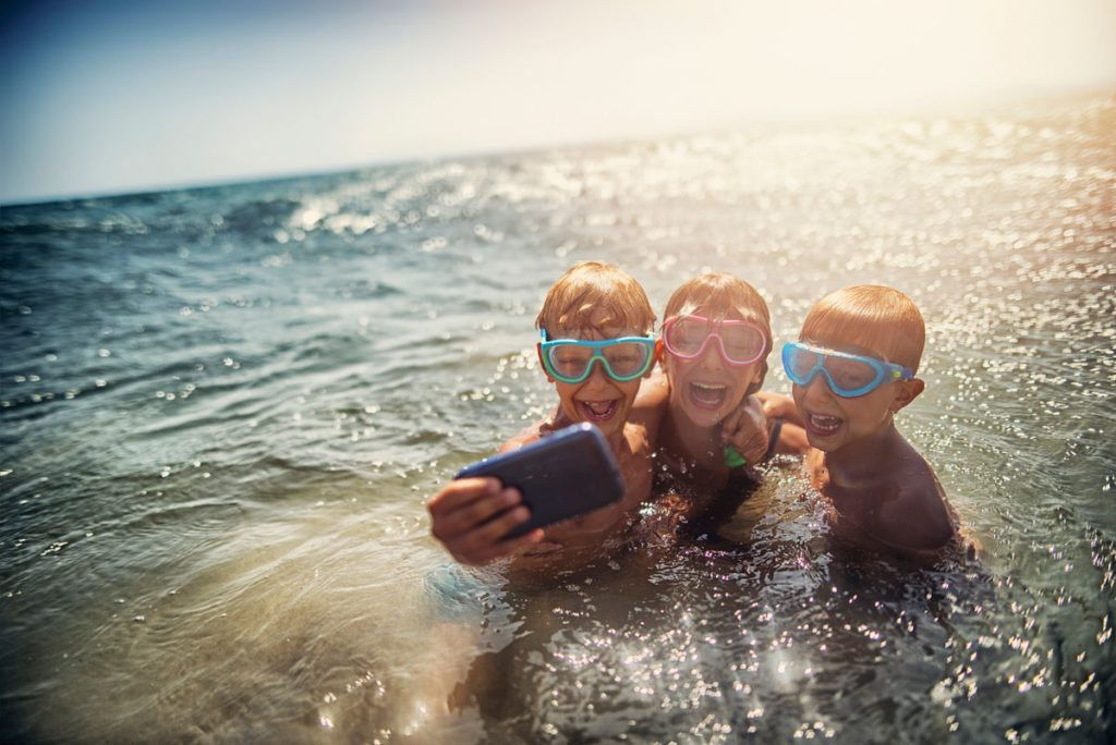 A group of kids taking a selfie in the ocean | Motif