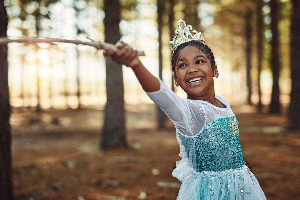 A little girl dressed as a princess playing in the woods | Motif