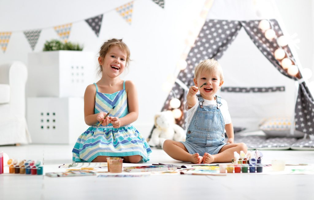 Two children painting in their playroom | Motif