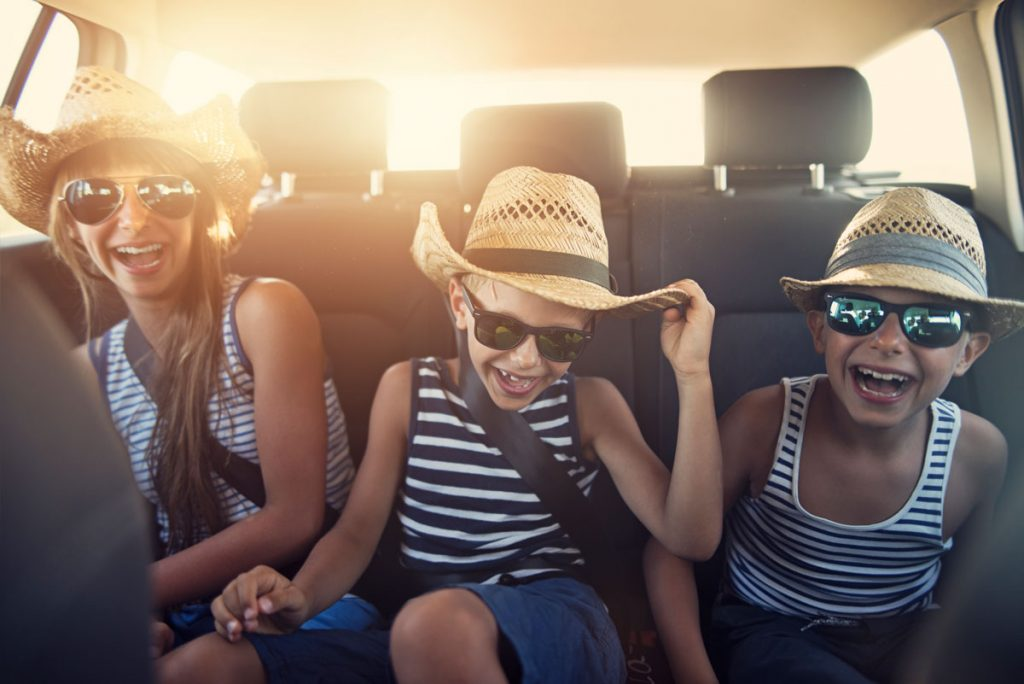 Three kids sitting in the back seat of a car | Motif