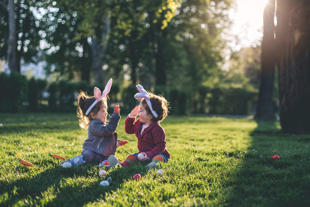Two very young kids high-fiving during an Easter egg hunt | Motif