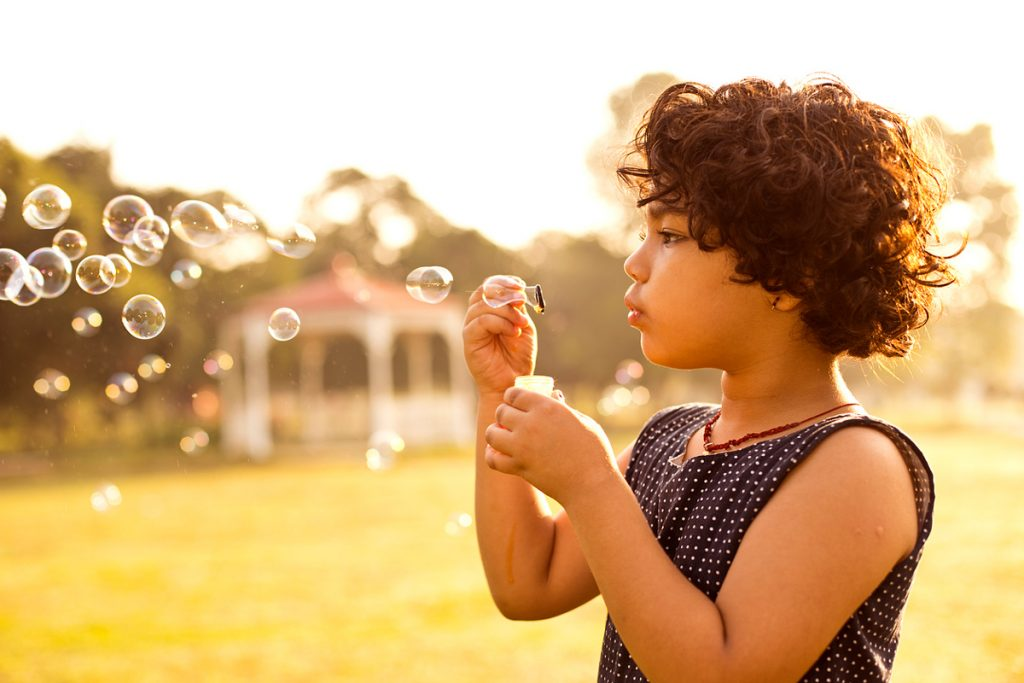 A girl blowing bubbles in a field | Motif