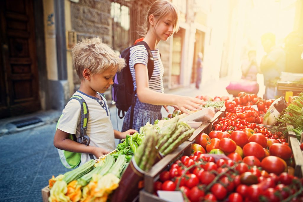 Kids picking out produce at the farmer's market.