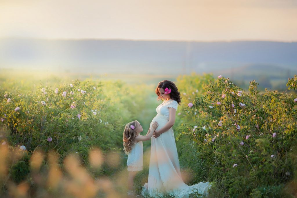 A pregnant mother in a field with her daughter | Motif