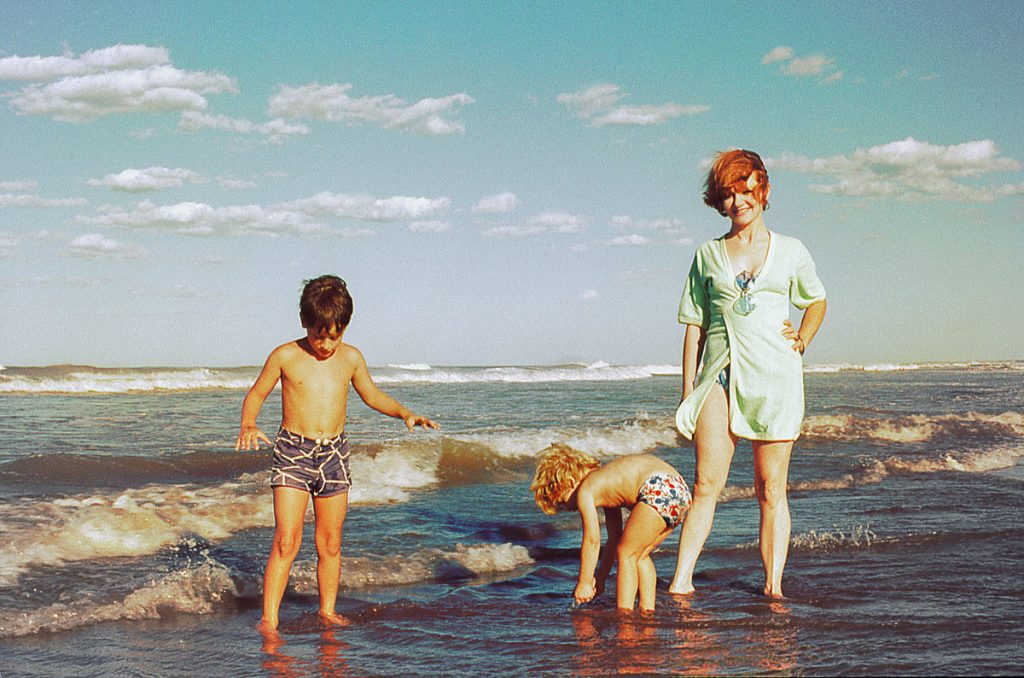A mom and two kids playing on the beach | Motif