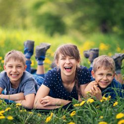 Three kids laying down in a sunflower field | Motif