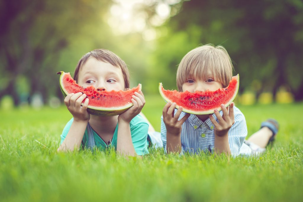 Two kids eating large watermelon slices | Motif