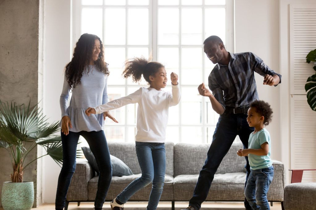 A family dancing in their living room in front of their couch | Motif