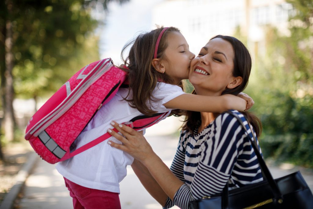 Mom gets a kiss before dropping daughter off at school