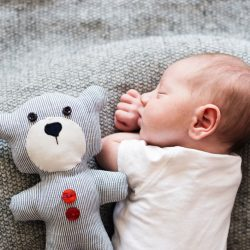 Newborn baby boy sleeping next to teddy bear.