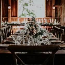 A long table with glassware and flowers on top | Motif