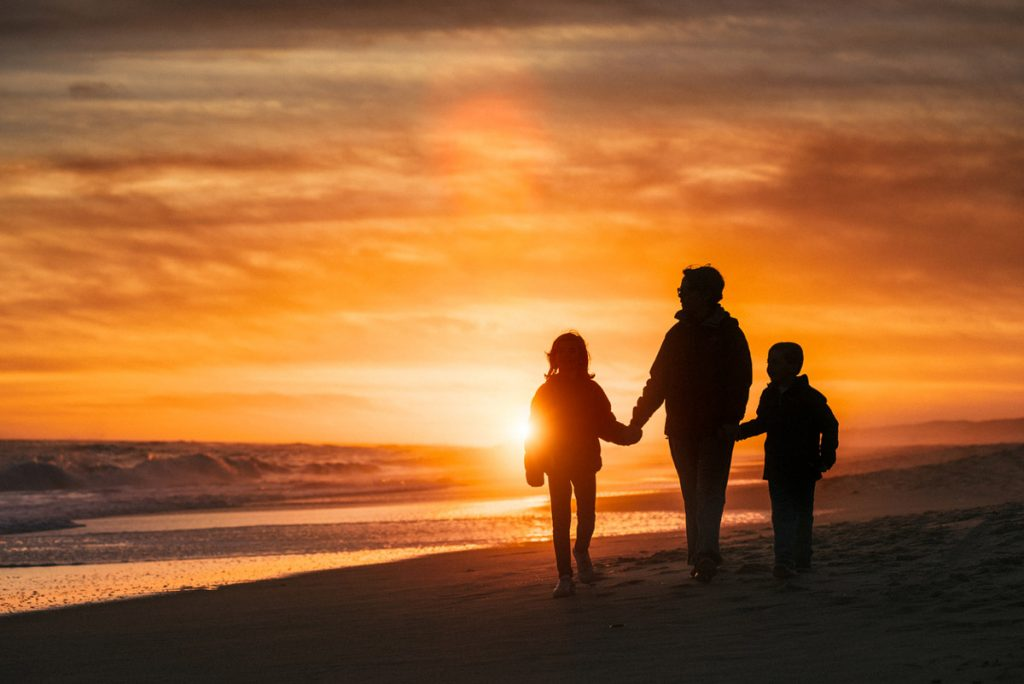 A silhouette of a family walking on the beach | Motif