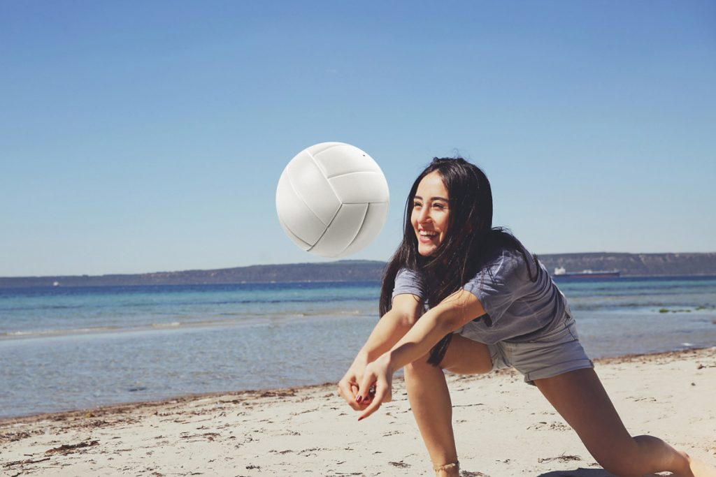 A woman playing beach volleyball | Motif