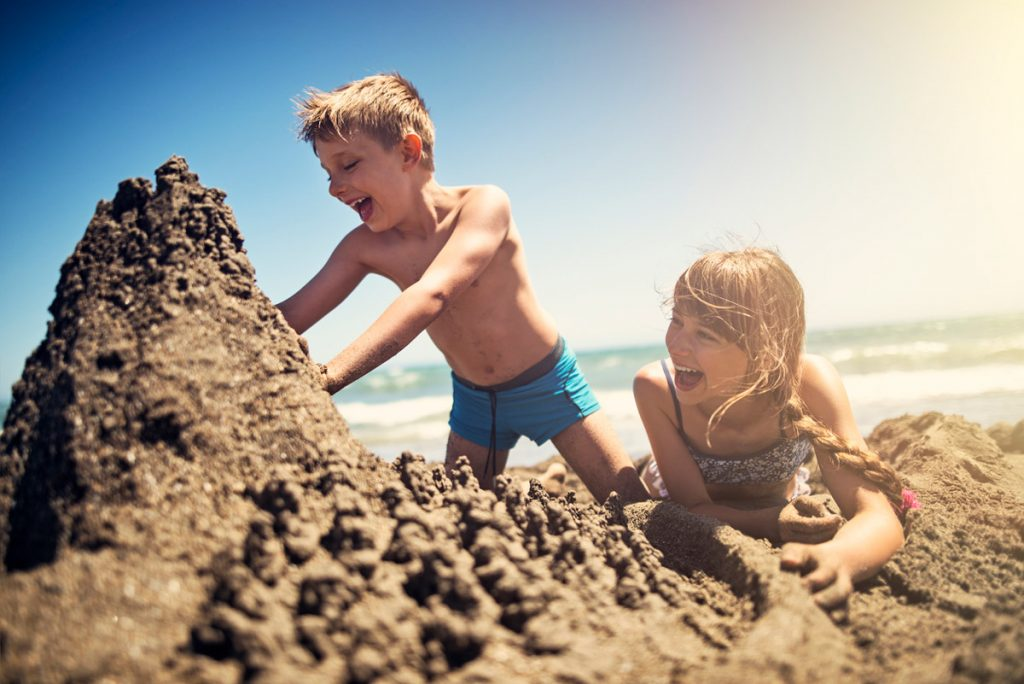 Brother and sister building a sandcastle | Motif
