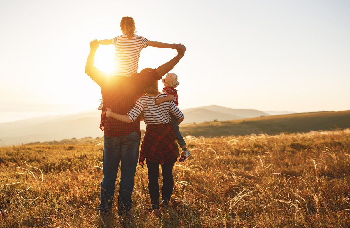 A family in a large field with the sun directly behind them | Motif