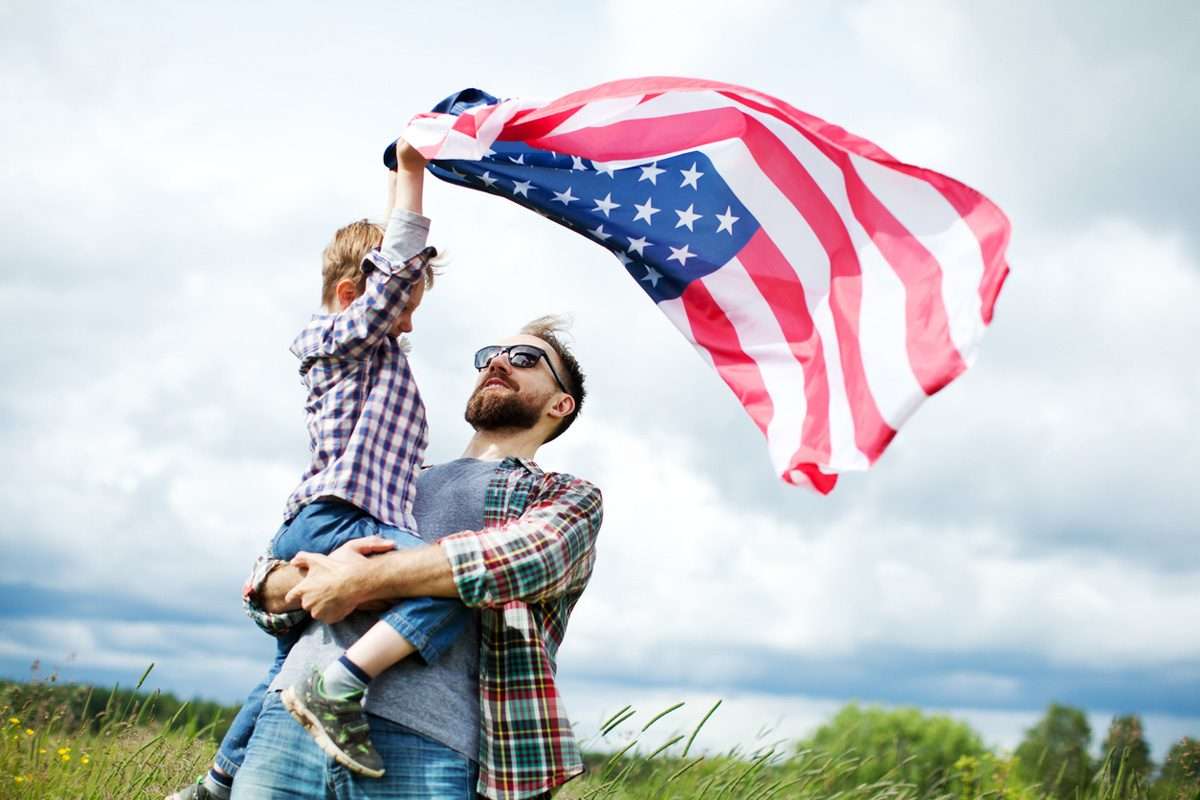A father holding his son who is holding an American Flag | Motif
