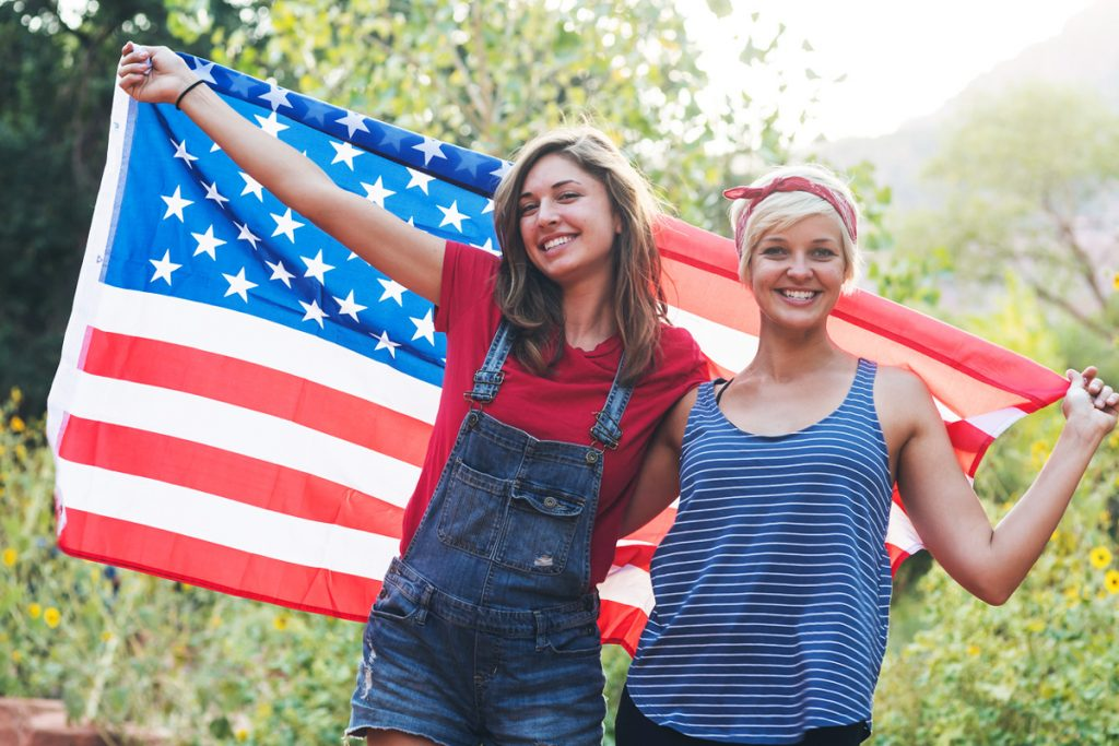 Two sisters holding an American Flag | Motif