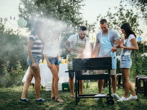 Friends standing around the grill at summer barbecue.