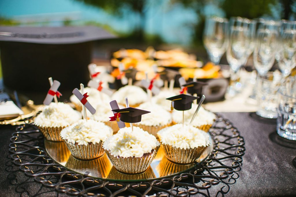A table of graduation cupcakes and champagne glasses | Motif