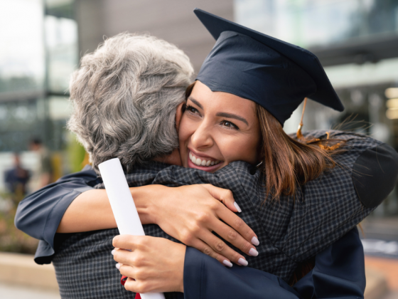 A college graduate hugging her mother | Motif