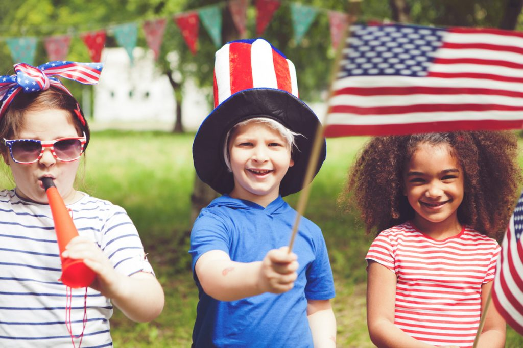 Kids waving small American Flags and wearing America accessories | Motif