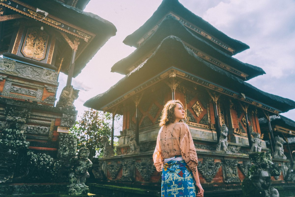 Woman walking in front of a Balinese temple