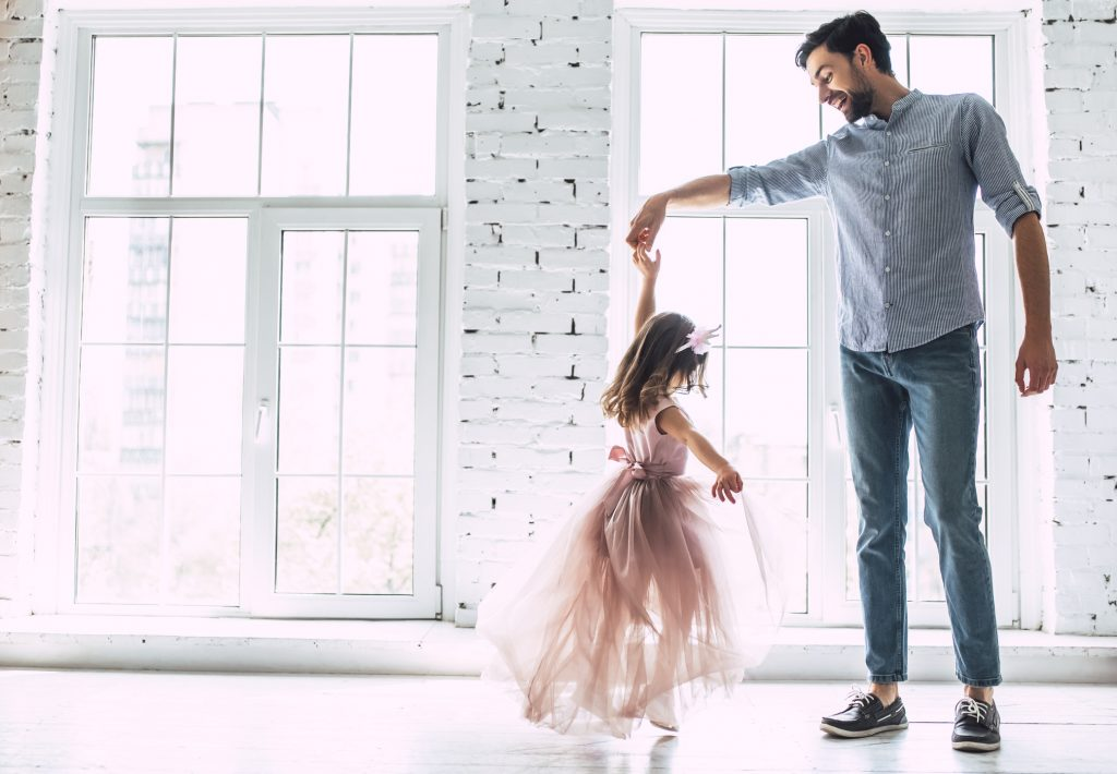 A father dancing at home with his daughter | Motif
