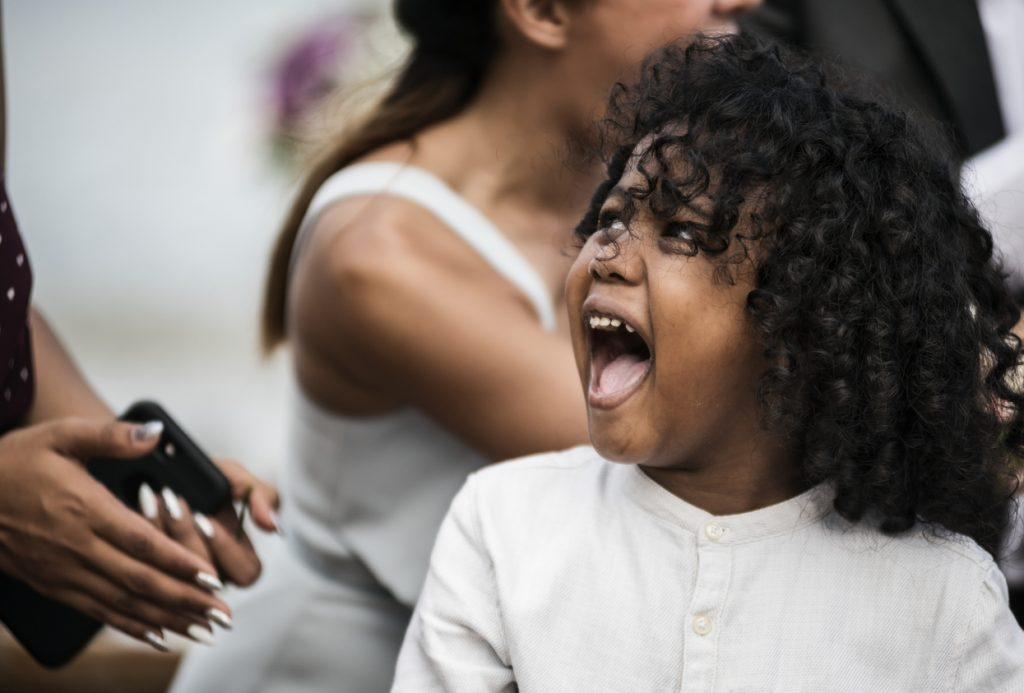 A candid photo of a little girl excited at a wedding | Motif