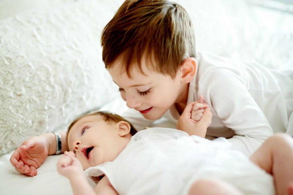 A baby announcement picture of an older brother lying with his baby sibling | Motif